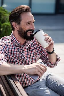 Poranny drink. wesoły dorosły człowiek odpoczywa na ławce podczas picia kawy