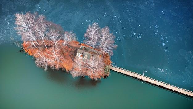 Poranny krajobraz, drewniana chata myśliwska, na małej sztucznej wyspie. nadchodzi drewniana platforma, po obu stronach rosną brzozy