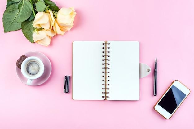 Poranny kubek kawy na śniadanie, ephone, notatnik, ołówek i róża na różowym stole