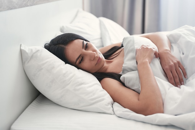 Poranny relaks. urocza brunetka pogrążona w myślach podczas leniwego poranka w domu
