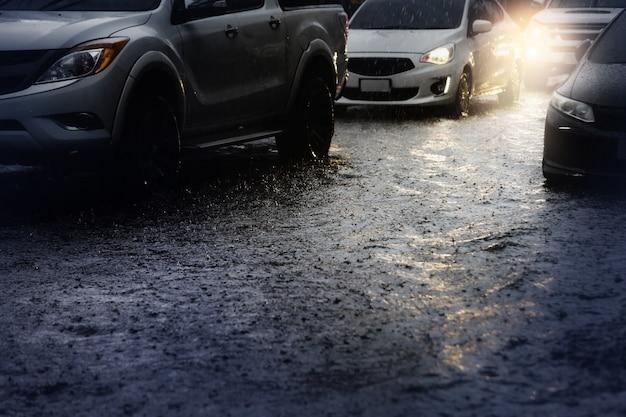 Poranny ruch w deszczowy dzień z ulewnym deszczem i powodzią w mieście, selektywne skupienie.