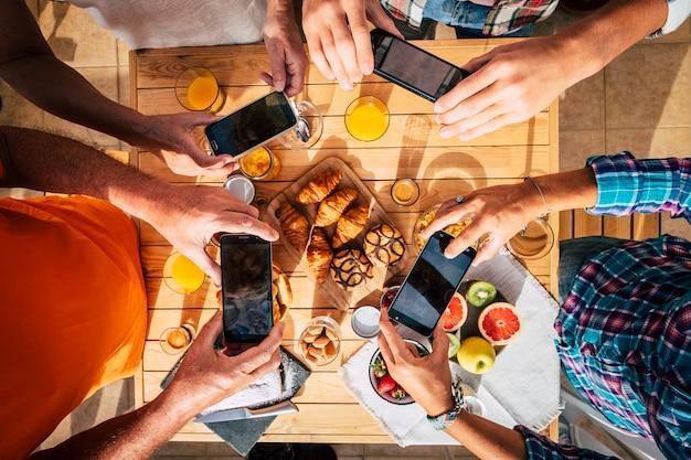 Poranny stół śniadaniowy pełen kawy i jedzenia, oglądany z góry pionowo powyżej, z grupą ludzi, którzy wspólnie bawią się i robią zdjęcia telefonami komórkowymi, aby podzielić się nimi w internecie. kolorowa powierzchnia