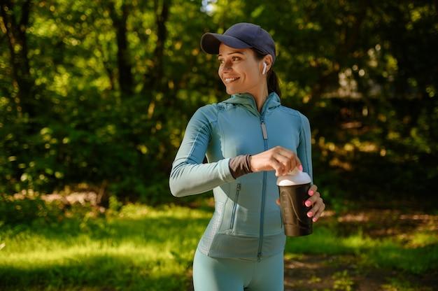 Poranny trening fitness w parku, uśmiechnięta kobieta w słuchawkach posiada wodę