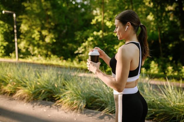 Poranny trening w parku, kobieta w słuchawkach pije wodę na chodniku. kobieta biegacz idzie do sportu w słoneczny dzień