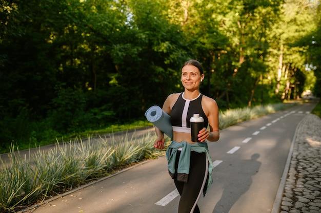 Poranny trening w parku, kobieta z matą i wodą na chodniku. kobieta biegacz idzie do sportu w słoneczny dzień