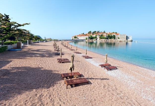 Poranny widok na morską wysepkę sveti stefan z różową piaszczystą plażą sveti stefan (czarnogóra, 6 kilometrów na południowy wschód od budvy)