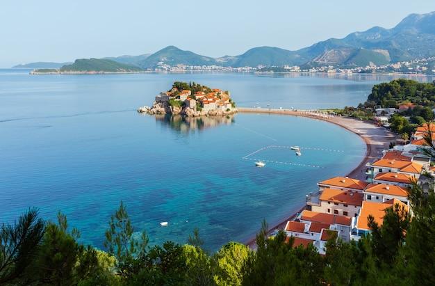 Poranny widok na morską wysepkę sveti stefan z różową plażą (czarnogóra, okolice budvy). ludzie są nie do poznania.