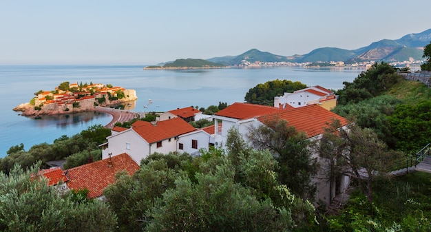 Poranny widok na morską wysepkę sveti stefan z różową plażą (czarnogóra, okolice budvy)