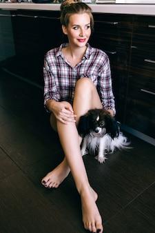Poranny zmysłowy portret ładnej blondynki bawiącej się w kuchni z małym psem, siedzącej na podłodze w kraciastej koszuli, przytulna atmosfera, delikatne kolory z filmu vintage.
