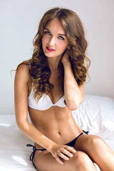 Poranny zmysłowy seksowny portret oszałamiającej młodej kobiety właśnie obudził się w białej sypialni, ciesz się porannym czasem, ubrana w uroczą swobodną bieliznę, stylowy makijaż, delikatne pastelowe kolory.