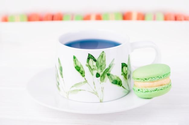 Porcelanowa filiżanka tajskiej herbaty z kwiatem grochu niebieskiego motyla i makaronik z zieloną miętą lub makaronik