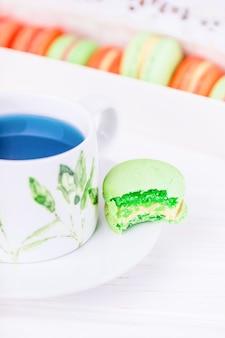 Porcelanowa filiżanka tajskiej herbaty z kwiatem grochu niebieskiego motyla i ugryziony zielony makaronik lub makaronik. skopiuj miejsce