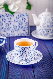 Porcelanowa filiżanka zielonej herbaty i imbryk