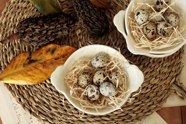 Porcelanowe miseczki w kremowym kolorze z jajkami kuropatwy. widok z góry.