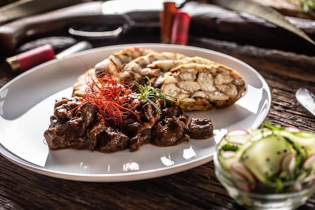 Porcelanowy talerz pełen gulaszu z jelenia z dziczyzny podawany z knedlami i świeżą sałatką jako przekąska. jedzenie otoczone jest akcesoriami myśliwskimi, takimi jak strzelba myśliwska, kule i nóż wiejski.