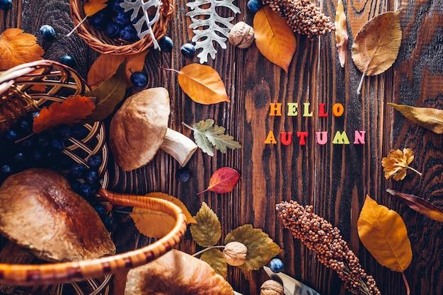 Porcini ono rozrasta się w koszu z jagodami i dokrętkami na drewnianym stole. jesienne zbiory. pisanie hello autumn