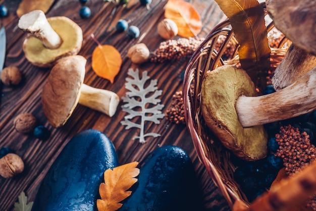 Porcini ono rozrasta się w koszu z jagodami i dokrętkami na drewnianym stole. jesienne zbiory z butami. zebrane jesienne plony