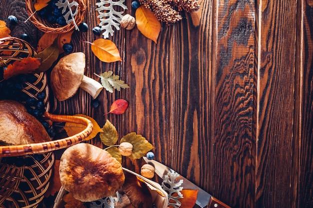 Porcini ono rozrasta się w koszu z jagodami i dokrętkami na drewnianym stole. jesienne zbiory. zebrane jesienne plony.