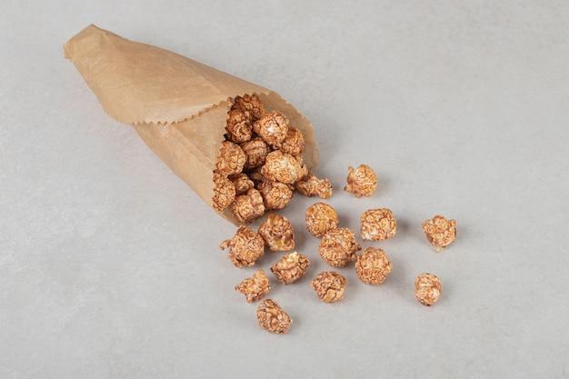 Porcja cukierków popcornowych w papierowym opakowaniu na marmurze.