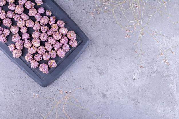 Porcja cukierków popcornu na tacy na marmurowym tle. zdjęcie wysokiej jakości
