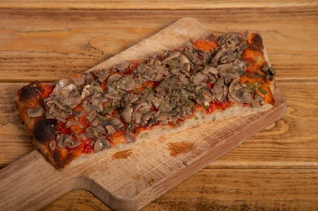 Porcja domowej roboty pizza z pieczarkami na drewnianej desce do krojenia.