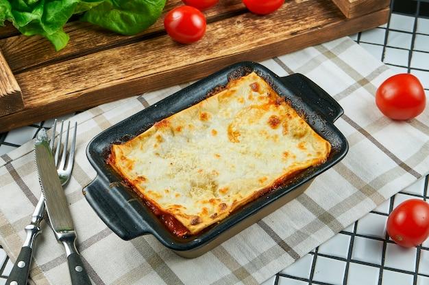 Porcja domowej włoskiej lasagne z serem, białym sosem i kurczakiem na białej szmatce. tradycyjny włoski makaron. biały stół