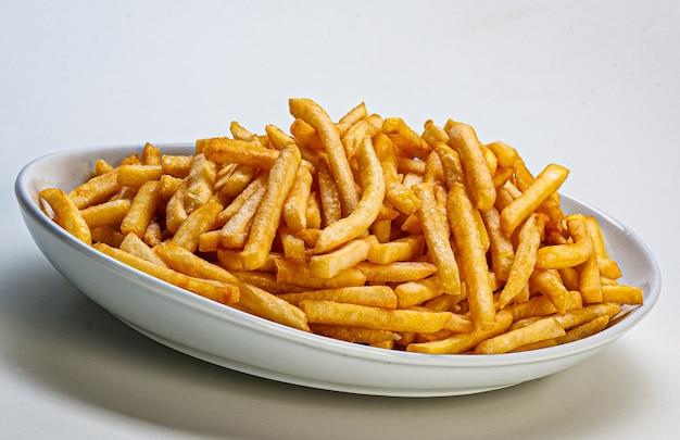 Porcja frytek podawana na talerzu na białym tle.