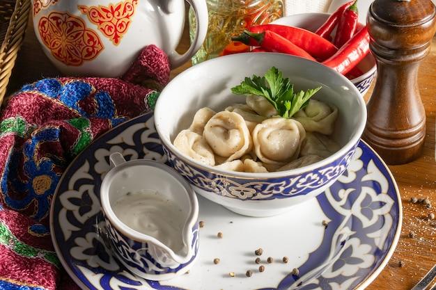 Porcja gotowanych pierogów ze śmietaną, natką pietruszki i przyprawami na talerzu z tradycyjnym uzbeckim wzorem