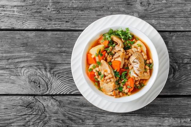 Porcja gulaszu z białej fasoli, warzyw i steku wieprzowego w białej misce na szarym stole rustykalnym, widok z góry, płasko ułożona, wolna przestrzeń