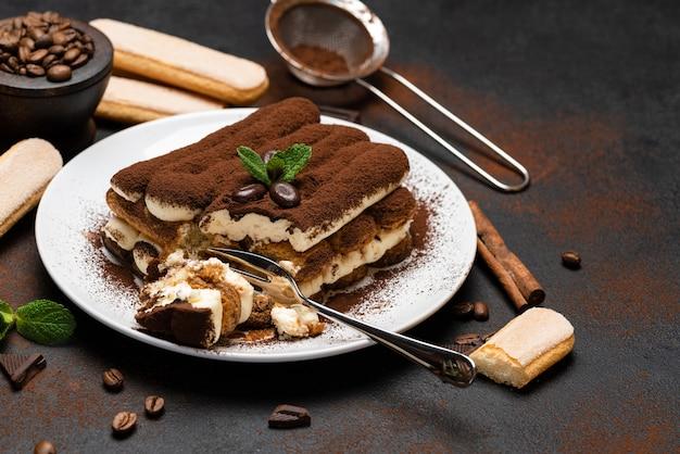 Porcja klasycznego deseru tiramisu i ciasteczka savoiardi na betonowym tle