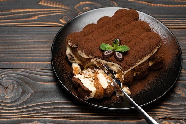 Porcja klasycznego deseru tiramisu na talerzu ceramicznym