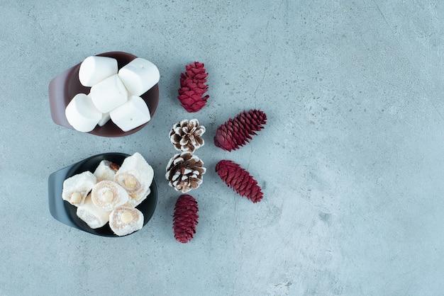 Porcja lokumów i marshmallows obok wiązki szyszek sosnowych na marmurze.