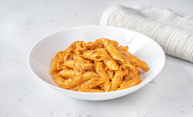 Porcja makaronu penne z sosem pomarańczowym pesto z bliska