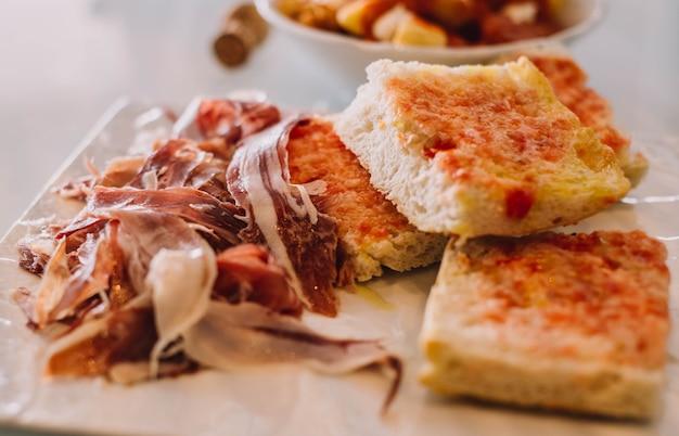 Porcja najlepszej jakości szynki iberyjskiej w towarzystwie domowych tostów z chleba