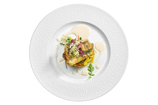 Porcja okonia morskiego z grilla z warzywami w białym talerzu. na białym tle na białej powierzchni. widok z góry