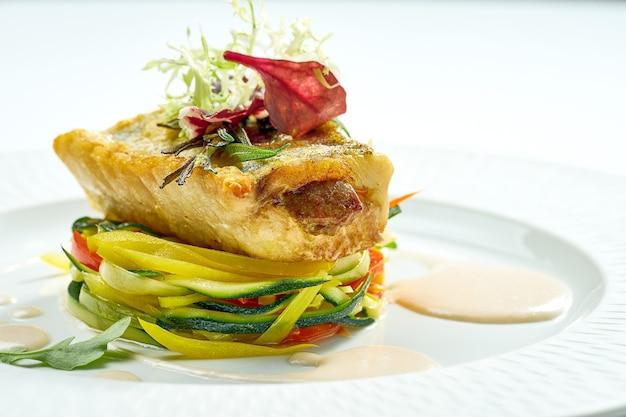 Porcja okonia morskiego z grilla z warzywami w białym talerzu. na białym tle na szarej powierzchni.