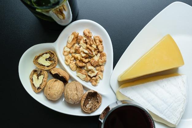Porcja orzechów obok parmezanu i sera brie, kieliszek i butelka czerwonego wina (widok z góry).