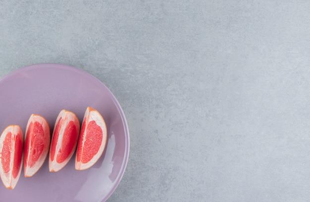 Porcja plasterków grejpfruta na talerzu na marmurze
