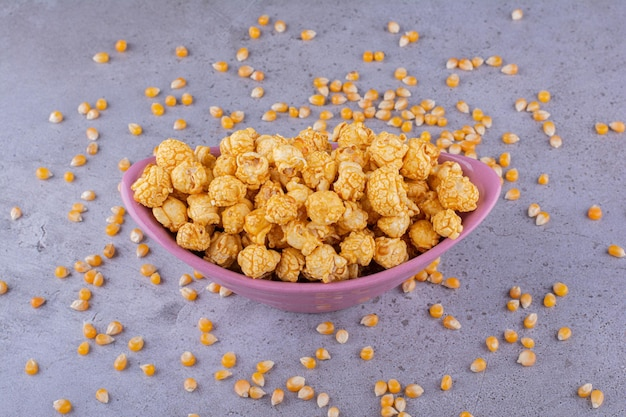 Porcja popcornu karmelowego z ziarnami kukurydzy rozsianymi na marmurowym tle. zdjęcie wysokiej jakości