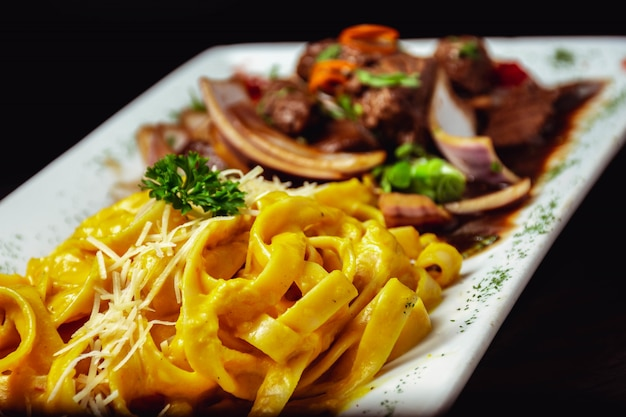 Porcja pysznego makaronu z sosem serowym i smażonym mięsem