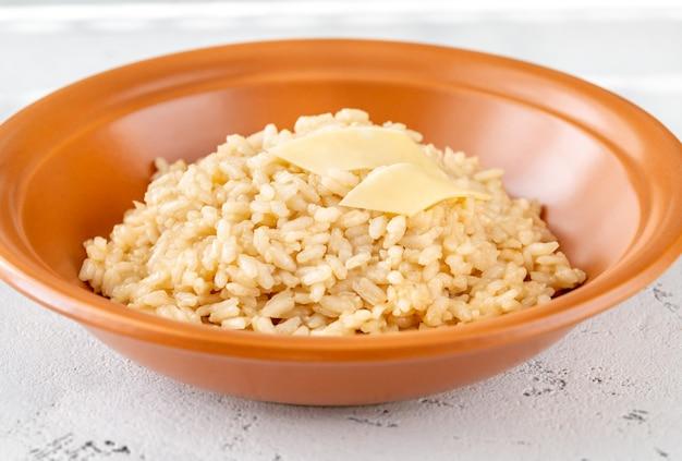 Porcja risotto przyozdobiona kawałkami parmezanu