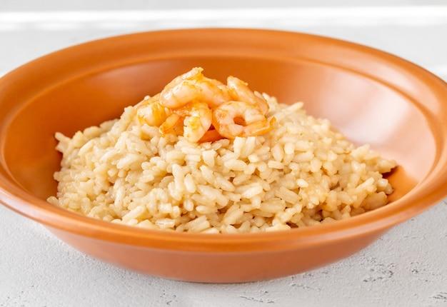 Porcja risotto przyozdobiona krewetkami w misce