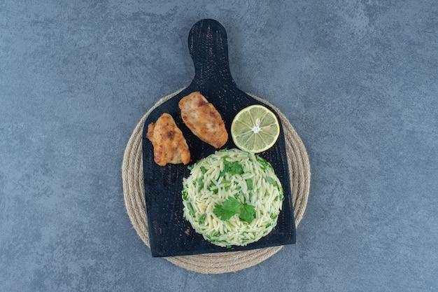 Porcja ryżu z bryłkami kurczaka na czarnej tablicy.