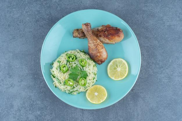 Porcja ryżu z udkami z kurczaka na niebieskim talerzu.