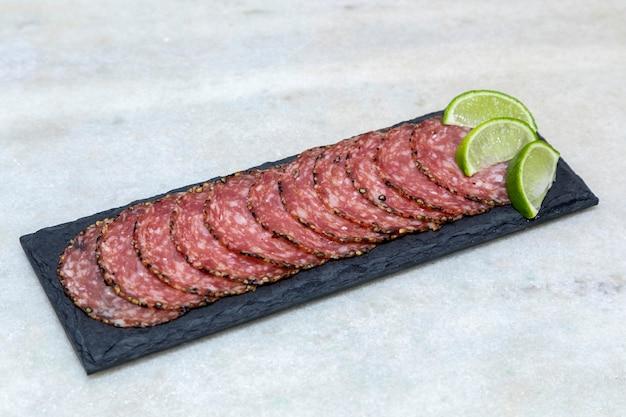 Porcja salami na czarnej kamiennej płycie