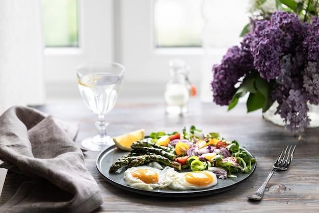 Porcja sałatki kukurydzianej z czerwoną cebulą, żółtymi pomidorami, szparagami i dwoma jajkami na talerzu na drewnianym stole.