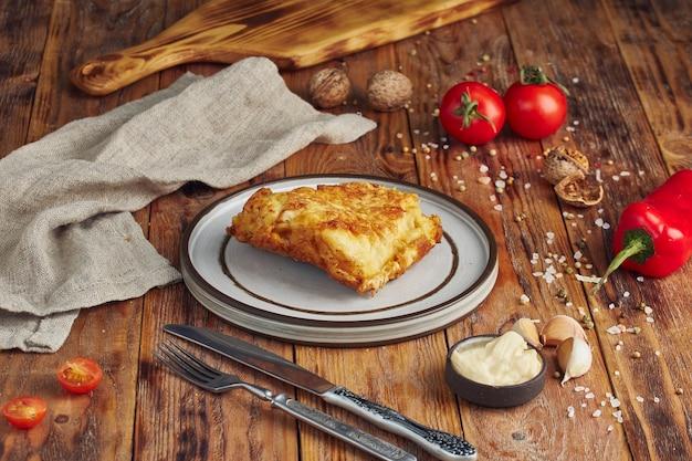 Porcja smażonego na patelni filetonu z morszczuka w panierce na drewnianym stole z serwetką