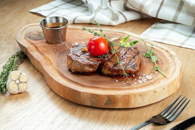 Porcja stek ribeye z grilla z sosem, pomidor na desce. obsługa restauracji drewniane tła. ścieśniać