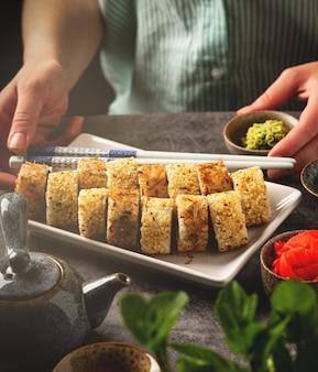 Porcja sushi toczy się na talerzu na stole, kobiece dłonie, zbliżenie