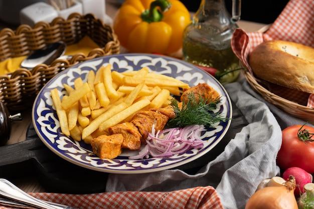 Porcja szaszłyka drobiowego z frytkami, cebulą i koperkiem na talerzu z tradycyjnym uzbeckim